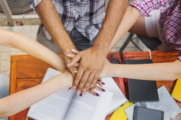 Studenti che impilano le mani sopra la tabella