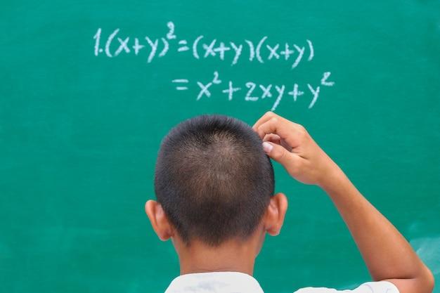 학생들은 수학 방정식과 지수로 교실에서 녹색 초크 보드 앞에 서 있습니다.