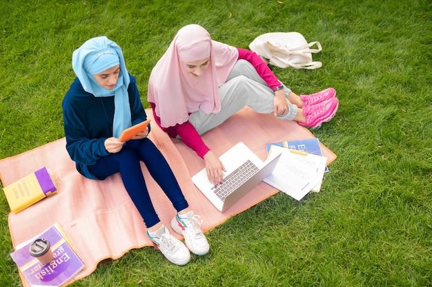 공부하는 학생. 대학 근처에 앉아 기기를 사용하여 공부하는 활동적인 무슬림 학생들