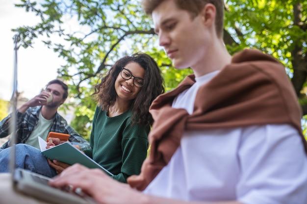 Студенты, обучающиеся в парке и выглядящие вовлеченными