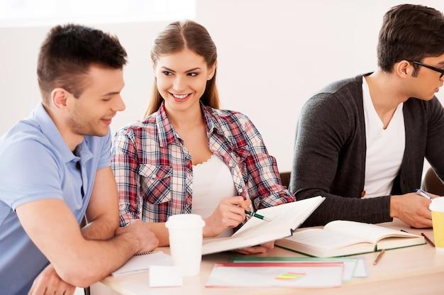 공부하는 학생들. 책상에 함께 앉아 공부하는 세 명의 자신감 있는 학생