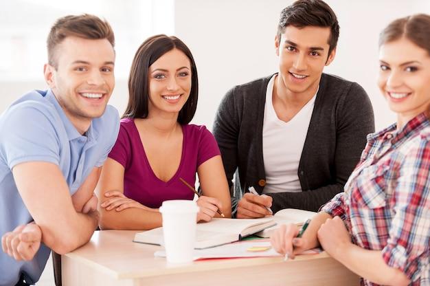 一緒に勉強している学生。一緒に机に座ってカメラに微笑んで勉強している4人の陽気な学生
