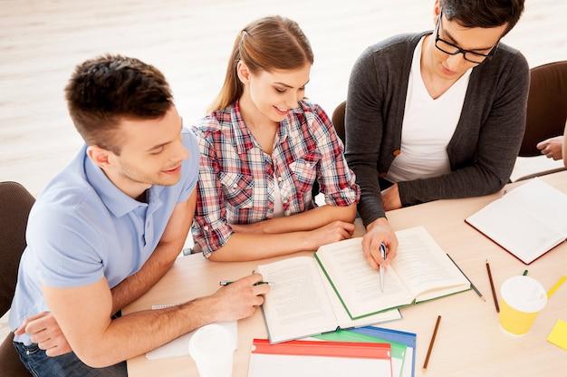 勉強している学生。一緒に机に座って勉強している3人の自信を持って学生の上面図