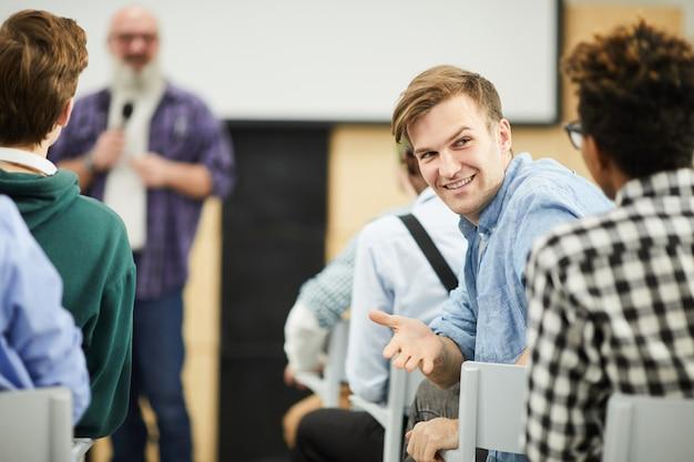 Студенты разговаривают в аудитории во время конференции