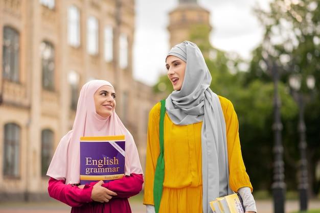 말하는 학생. 밝은 히잡을 입은 무슬림 학생들이 함께 대학에 걸어 가면서 이야기