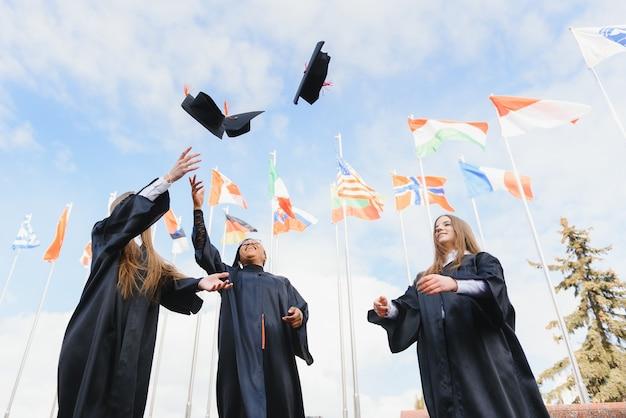 卒業式の帽子を空中に投げて祝う学生