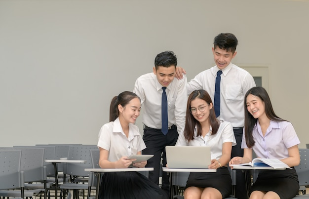 Students in uniform working with laptop