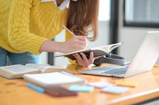 学生はラップトップを使用し、大学入試のためにメモを取ります。