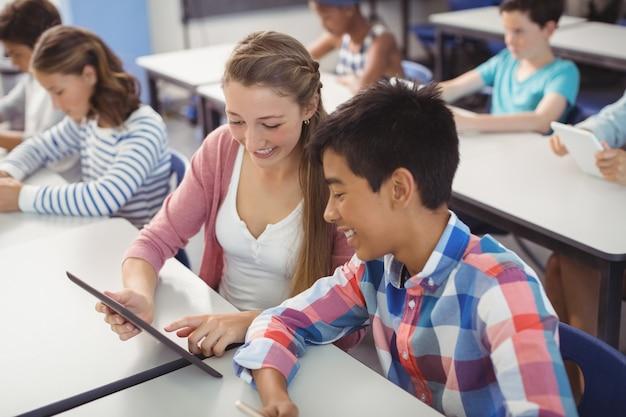 Студенты, использующие цифровой планшет и ноутбук в классе