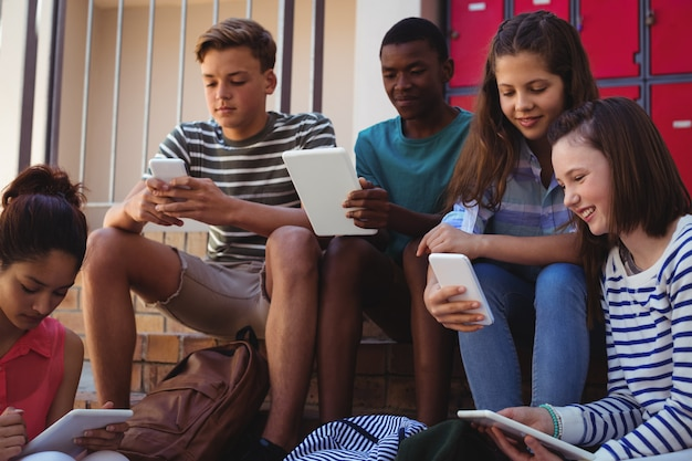 階段で携帯電話とデジタルタブレットを使用している学生