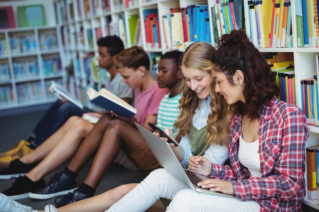 図書館で携帯電話とラップトップを使用している学生