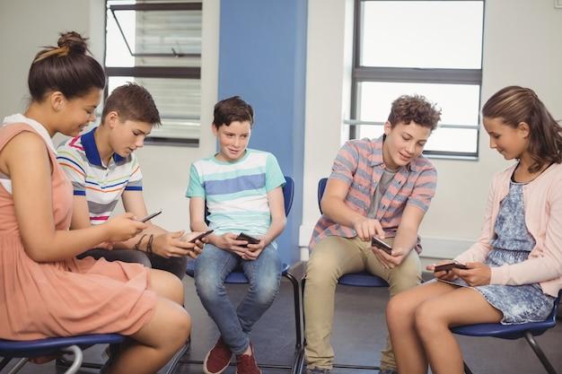 教室で携帯電話を使用している学生