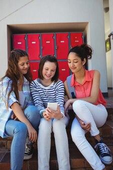 階段で携帯電話を使用している学生