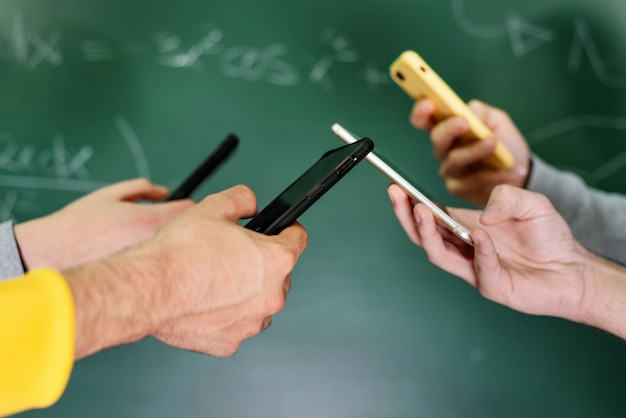 Students using mobile phones in classroom on chalkboard