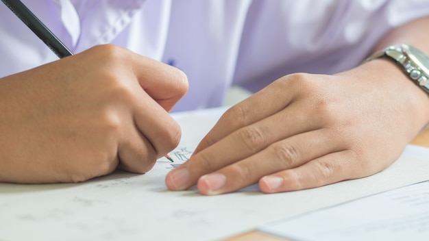 Students using pencil writing information on white answer paper in high school