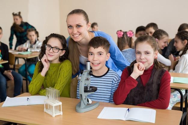 초등학교에서 과학 비커와 현미경을 사용하는 학생들