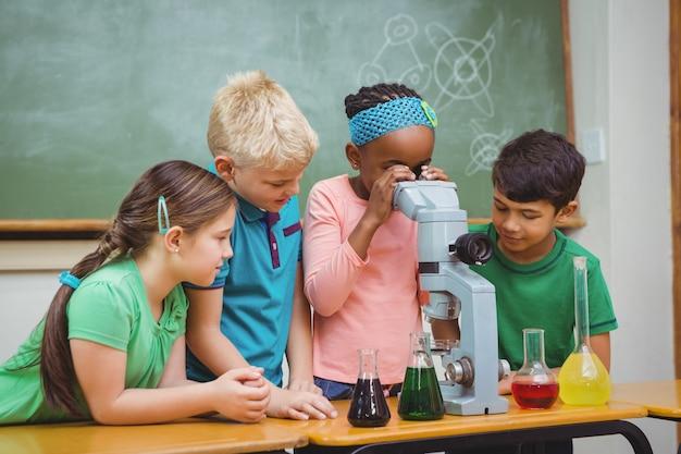 과학 비커와 현미경을 사용하는 학생들