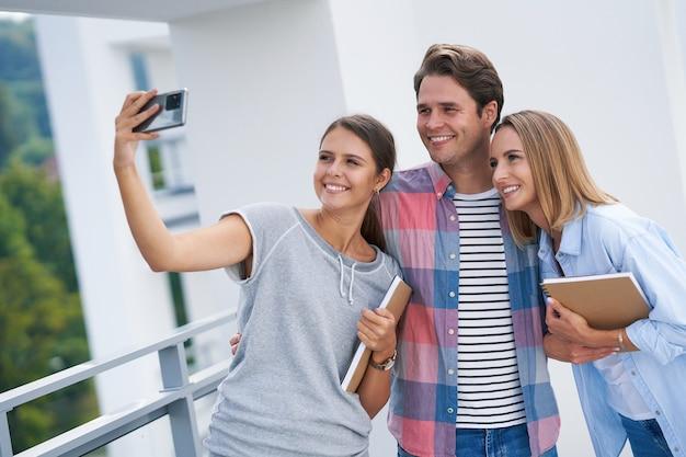 Студенты используют смартфон в кампусе