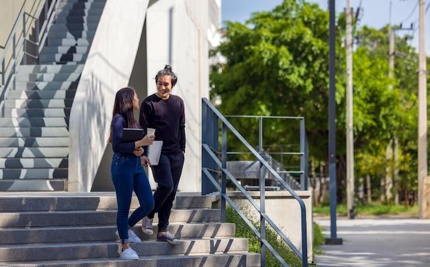 学生はキャンパスの階段を歩き、カップルは追加の教育のために地面に降りてきます。