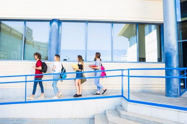 大学の建物の近くのランプで歩いている学生