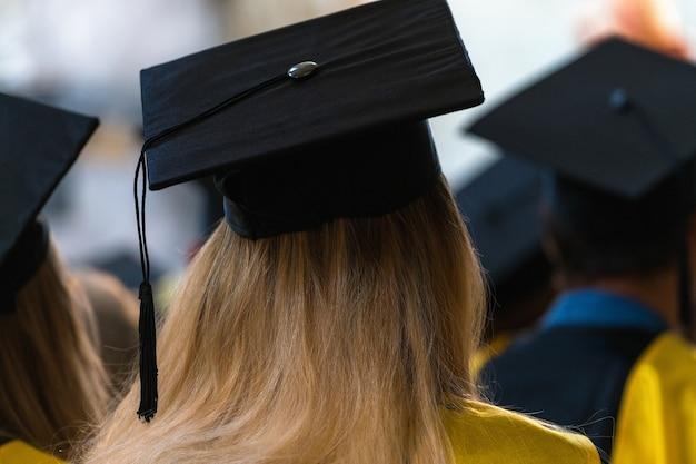 ガウンと帽子をかぶって室内に座り、卒業式の日に卒業証書を受け取るのを待っている学生。