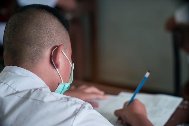 コロナウイルスまたはcovid-19を保護するためにマスクを着用し、ストレスのある学校の教室で試験解答用紙の演習を行う生徒。
