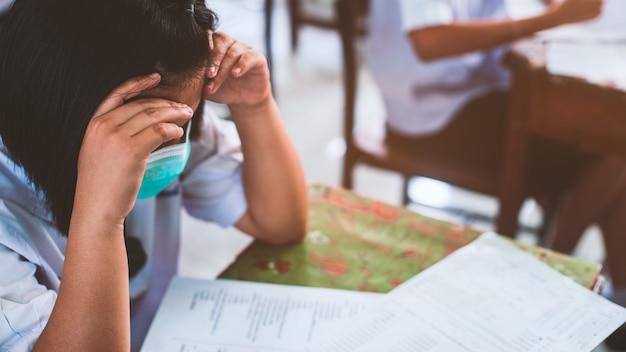 コロナウイルスやcovid-19を保護するためのマスクを着用し、ストレスのある学校の教室で試験解答用紙の演習を行う生徒。