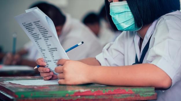 コロナウイルスまたはcovid-19を保護するためにマスクを着用し、試験解答用紙の演習を行う学生