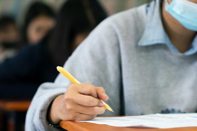 코로나 바이러스를 보호하기 위해 마스크를 쓰고 스트레스를받는 교실에서 시험을 보는 학생들