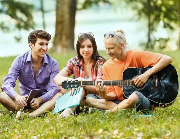 공원에서 쉬고 기타를 가진 학생