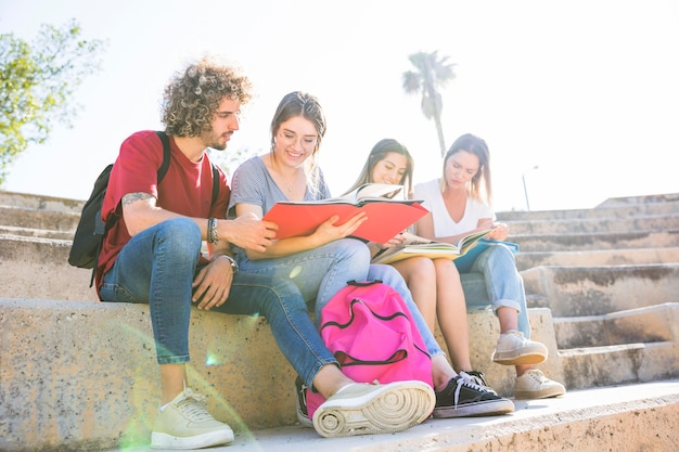 Students with backpack reading on steps