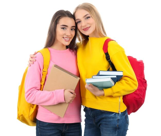 白のバックパックと本を持っている学生。