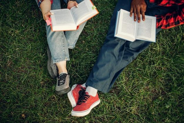 夏の公園の芝生で休んで本を持つ学生。