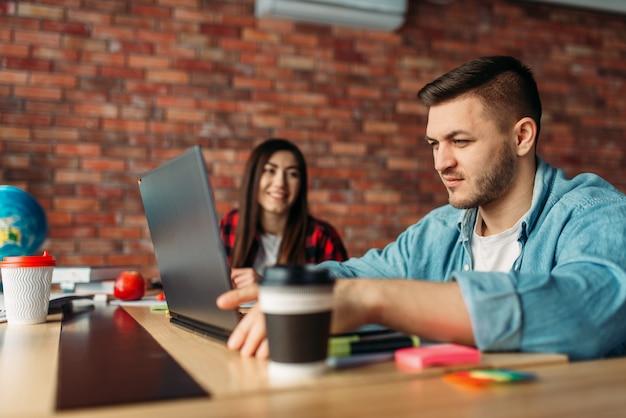 Студенты с компьютером вместе учатся за столом. люди с ноутбуком просматривают информацию в интернете