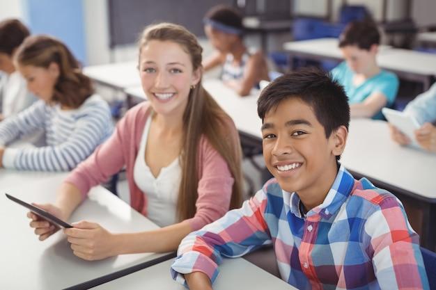 Студенты с цифровым планшетом и ноутбуком в классе