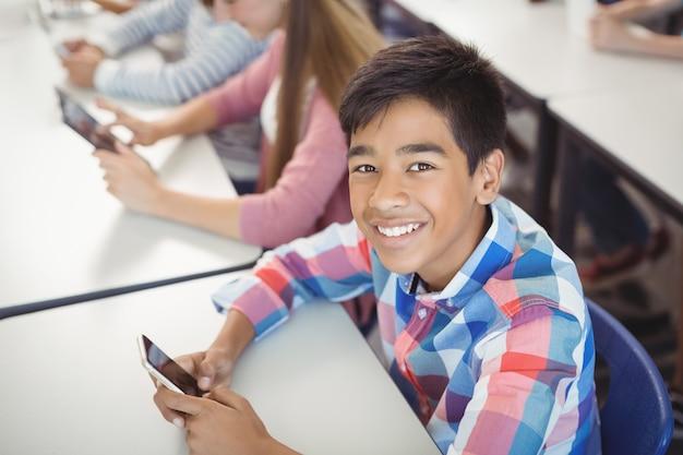 Студенты с цифровым планшетом и мобильным телефоном в классе