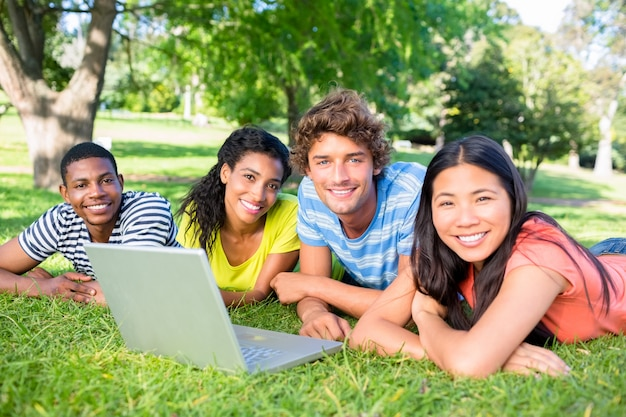 Students with laptop lying on campus