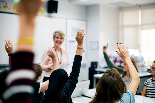 Students with their hands up responding to their teacher