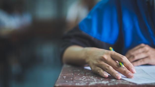 ストレスのある学校の教室で試験解答用紙の演習を書いたり読んだりする学生