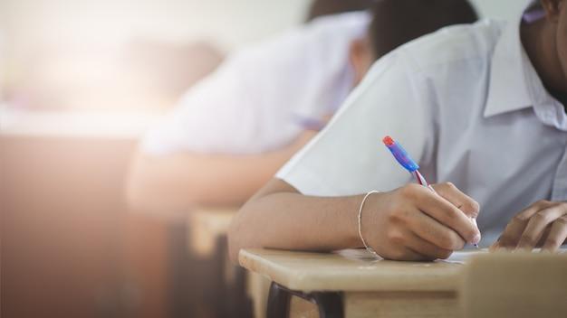 Студенты пишут и читают упражнения на листах с ответами на экзамен в классе школы со стрессом