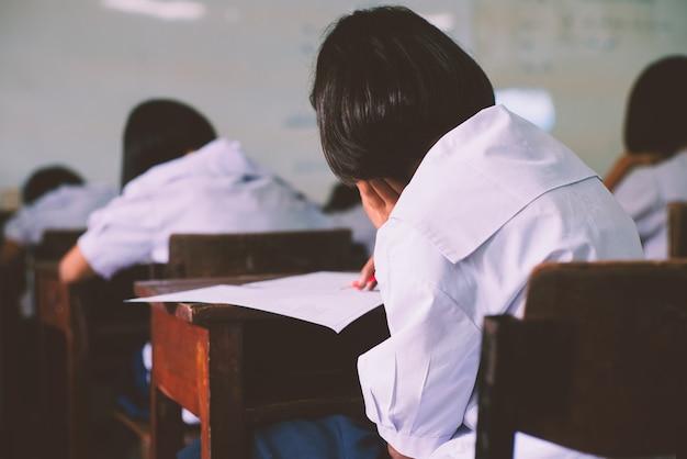 ストレスのある学校で生徒が試験の解答用紙を書き、読む