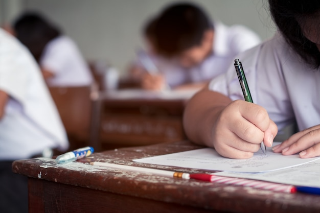 Students writing answer doing exam in classroom