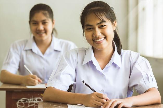 Студенты, пишущие перо в руке, делают экзамены, отвечают листам упражнений в классе с улыбкой и счастливы.