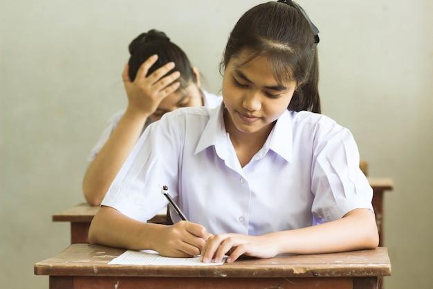 Студенты, пишущие перо в руке, делают экзамены, отвечают на листы упражнений в классе с улыбкой.