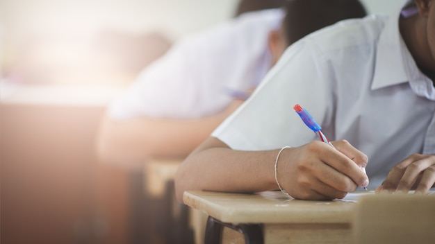 Students writing and reading exam answer sheets exercises in classroom of school with stress