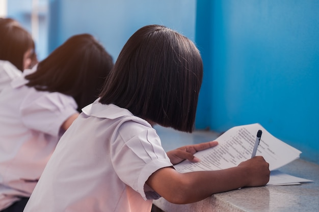 Students writing and reading exam answer sheets in school with stress