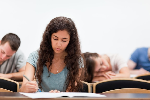 Students writing while their classmate is sleeping