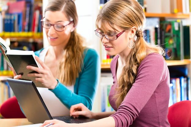 학생-그룹에서 랩톱 및 도서 학습 도서관에서 젊은 여성