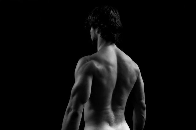 Studiio photography of a man with his back, white and black