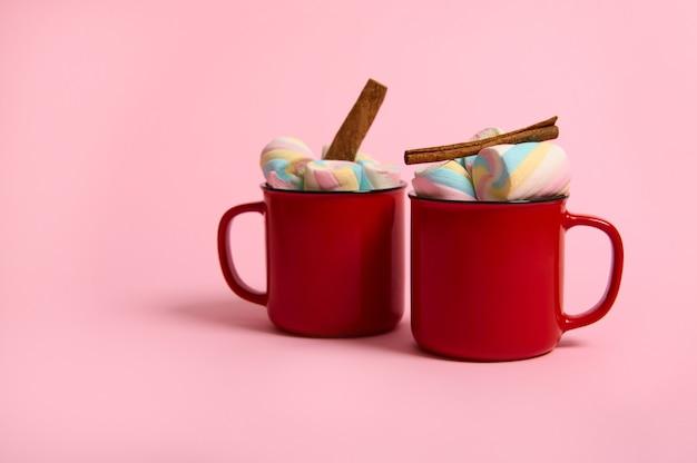 Студийная реклама выстрел красочного зефира и палочки корицы в чашке горячего шоколадного напитка в красных кружках, изолированных на розовом пастельном фоне с копией пространства для рождественской рекламы